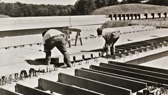 Workers laying a plywood base over joists